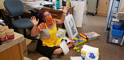 A library worker sits on the floor, assembling bags with summer reading craft materials.