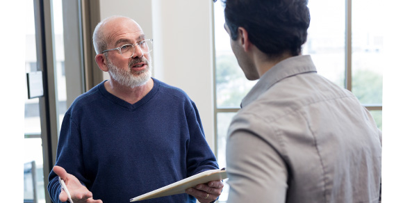 Older man with clipboard discusses information with younger man