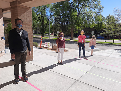 Library staff stand outside the library, aligned with ground marking indicating safe social distancing.